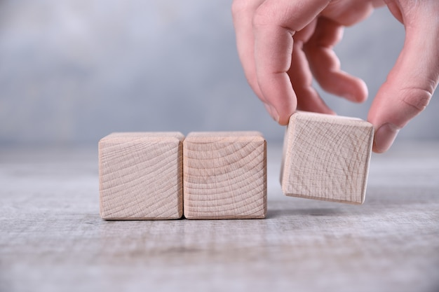 Hand puts blank wooden cube on the table