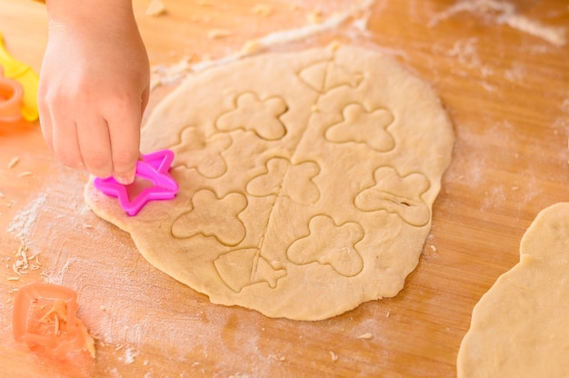 Hand puts butterfly shapes on dough