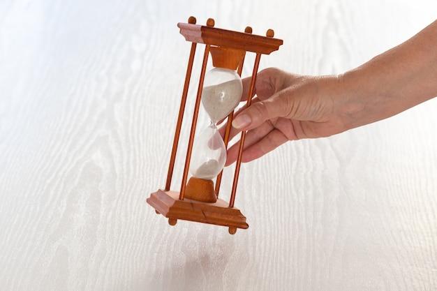 手が白い木製のテーブルに砂時計を置く