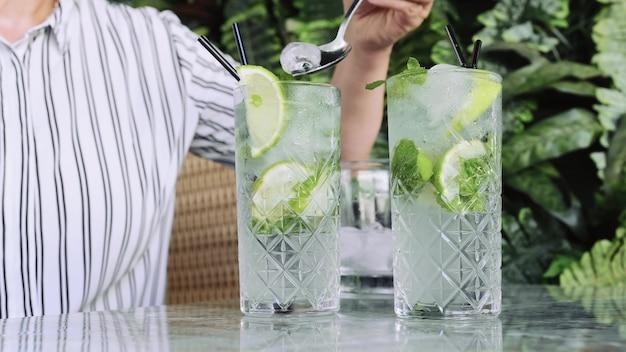 Рука ставит лед для коктейлей, джин-тоник или мохито с джином, мятой, льдом и лаймом на столе в кафе.