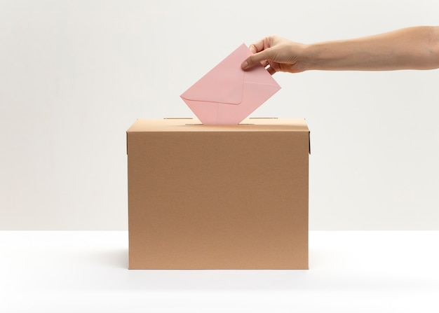 Hand puts pink envelope into vote box
