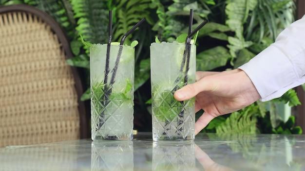Рука ставит два коктейля с джин-тоником или мохито с джином, мятой, льдом и лаймом на стол в кафе.