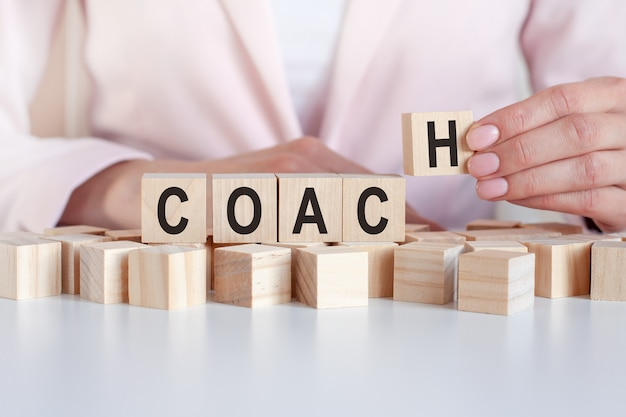 The hand puts a wooden cube with the letter coach