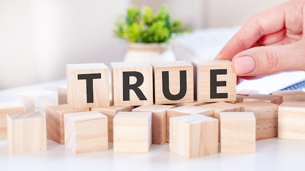 The hand puts a wooden cube with the letter e from the word true