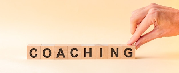 The hand puts a wooden cube with the letter g from the word coaching