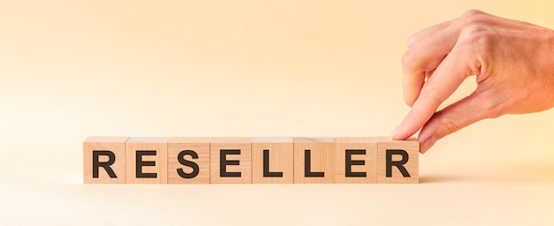 The hand puts a wooden cube with the letter r from the word reseller. the word is written on wooden cubes standing on the yellow surface of the table.
