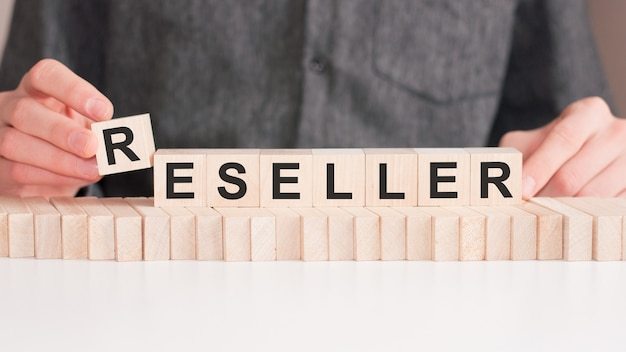 The hand puts a wooden cube with the letter r from the word reseller.