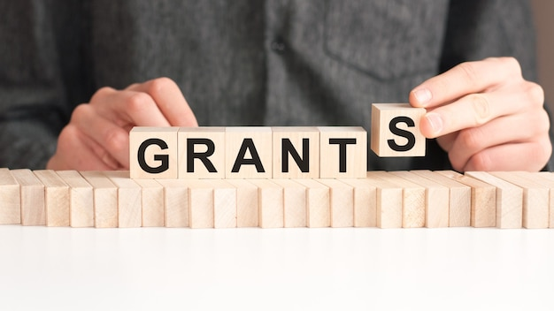 The hand puts a wooden cube with the letter s from the word grants. the word is written on wooden cubes standing on the white surface of the table.