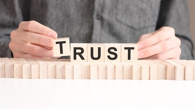 The hand puts a wooden cube with the letter t from the word trust