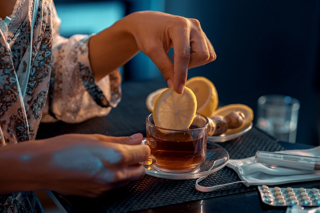 レモンのスライスをグラスに入れて手