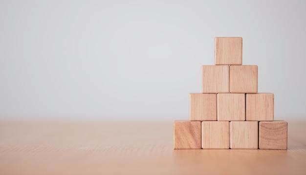 Рука кладет и укладывает пустые деревянные кубики на стол с копией пространства для ввода формулировок и значка инфографики.