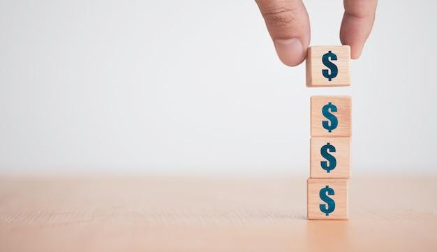 손을 넣어 나무 큐브 블록에 화면을 인쇄하는 달러 기호 또는 usd를 스태킹. 달러는 세계의 주요 환전 통화입니다.