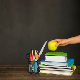 Hand putting apple on textbooks on workplace