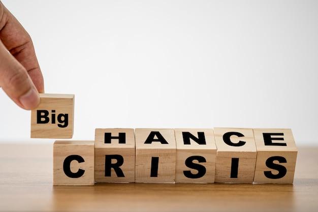 木製立方体のブロックに画面を印刷するチャンスと危機の言葉遣いのめくりに大きな言い回しを入れた手。