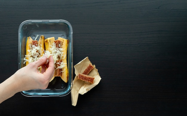 Рука положить сыр, чтобы приготовить спелый банан в духовке с гуавой и бутерброд с сыром на черном деревянном основании. типичная концепция латинской кухни. копировать пространство