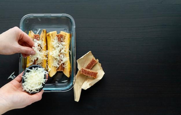 Рука кладет сыр для приготовления спелый банан в духовке с гуавой и бутербродом с сыром на черной деревянной основе