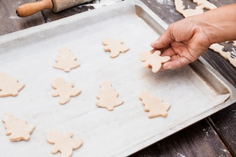 Hand putting Christmas shaped cookies on baking sheet