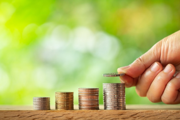 Hand putting coin on coins stack with greenery blurred background