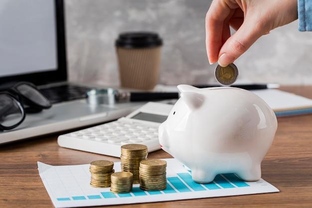 貯金箱と成長チャートにコインを入れる手