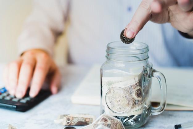 Рука кладет монету внутрь банки