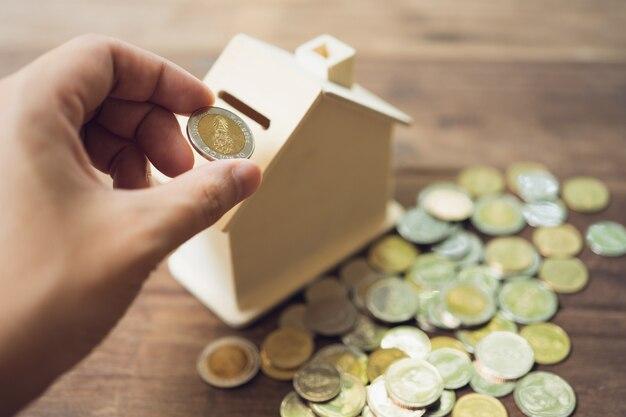 Hand putting coin inside money box