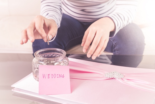 Hand putting a coin into glass jars with 'wedding' text