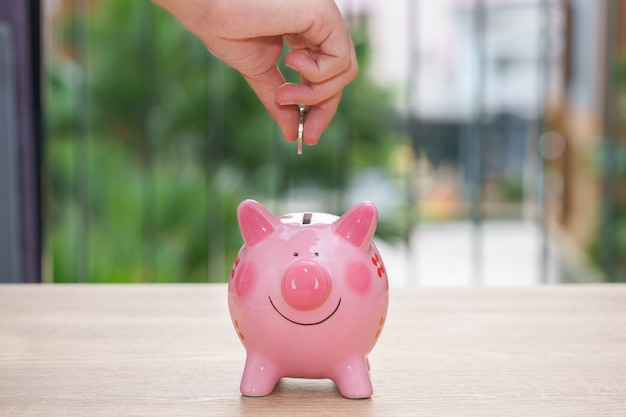 Hand putting a coin into a pink piggy bank on wooden desk - save money concept.