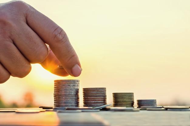 コンセプトとコインスタックにコインを置く手、お金と自然の夕日の背景を保存