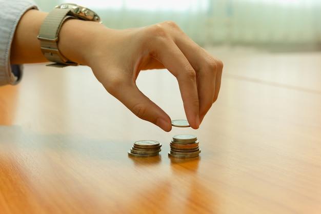 Рука кладет монетку на монеты, складывая с экономией, концепция финансов.