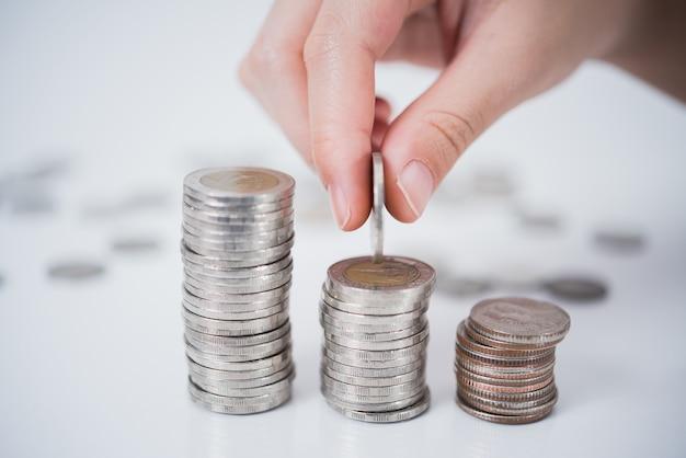 돈을 절약 흰색 배경에 동전을 넣어 손