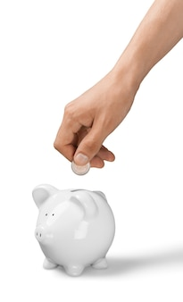 Hand putting coin to piggy bank and coins on white background