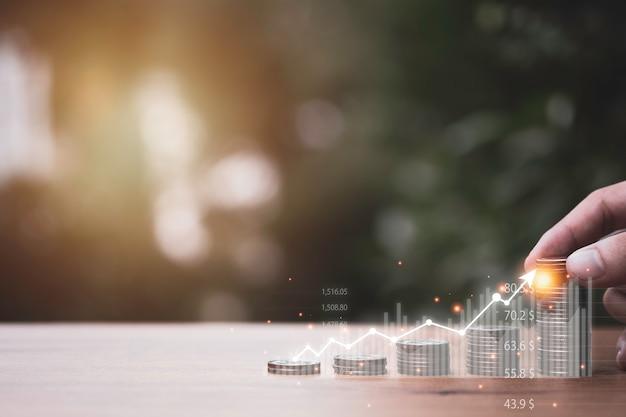 Рука, положить монеты, укладка с граф виртуальной тенденции на столе. бизнес рост инвестиций и концепция увеличения прибыли.