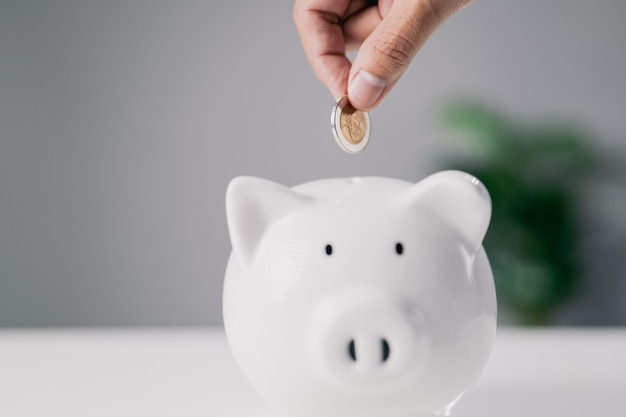 흰색 돼지 저금통에 동전을 넣고 복사 공간이 있는 책상에 있는 손 미래를 위한 돈 절약