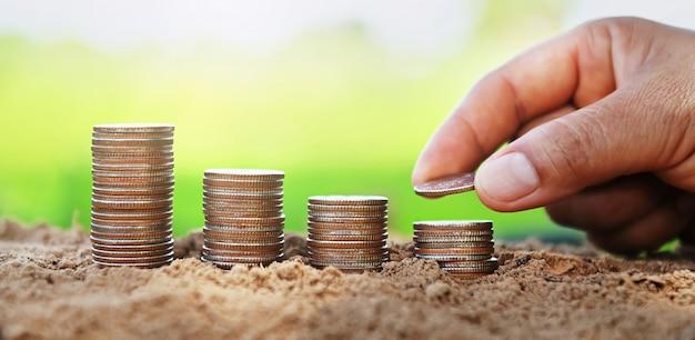 햇빛과 토양에 스택에 동전을 넣어 손.