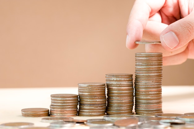 Hand putting coins stacking for saving in the future and fund stock value investment.