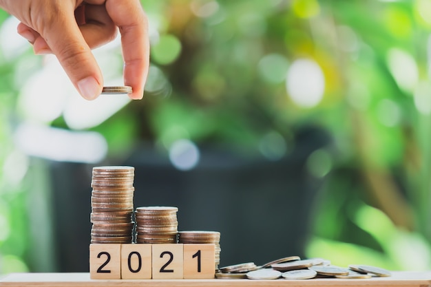 Hand putting the coins on the wooden table like a growing graph. with text 2021, on green blurry bokeh background.