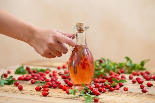 Рука кладет флягу с маслом розового шиповника на коричневый деревянный стол. рука с пальцами держит стеклянный флакон с розовым лосьоном из лесных ягод.