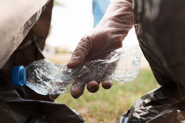 Hand putting empty plastic bottle in to garbage black bag