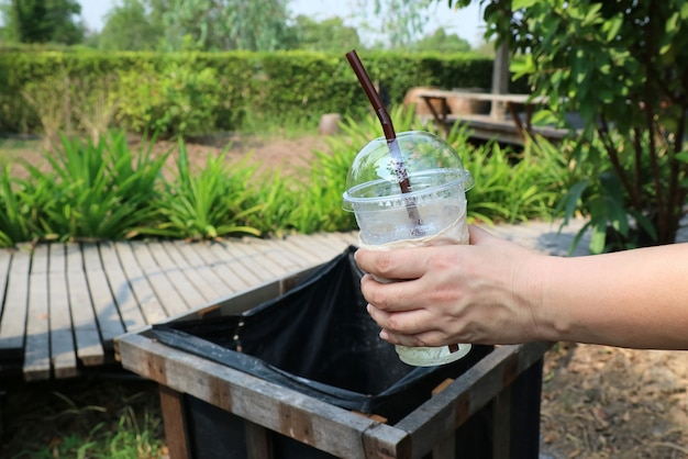 Hand putting empty plastic glass with straw into to wooden bin in the park.