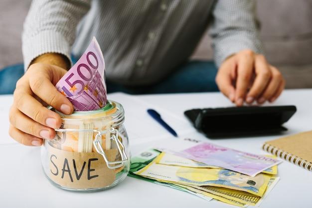 Рука положить банкноты евро в стеклянную банку для экономии. человек делает свой бухгалтерский учет