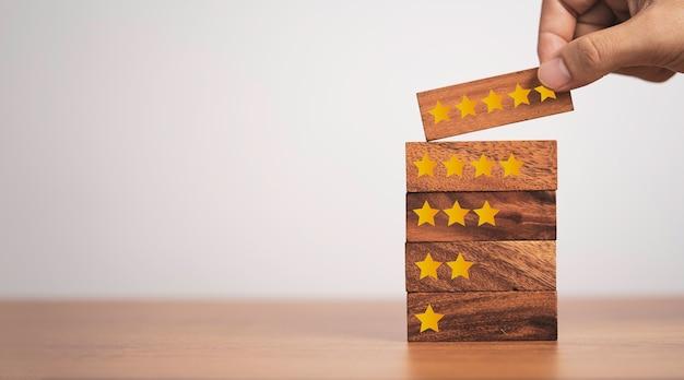 Рука помещает пять запусков, которые печатают экран на деревянном кубическом блоке, удовлетворенность клиентов продуктом и услугой.