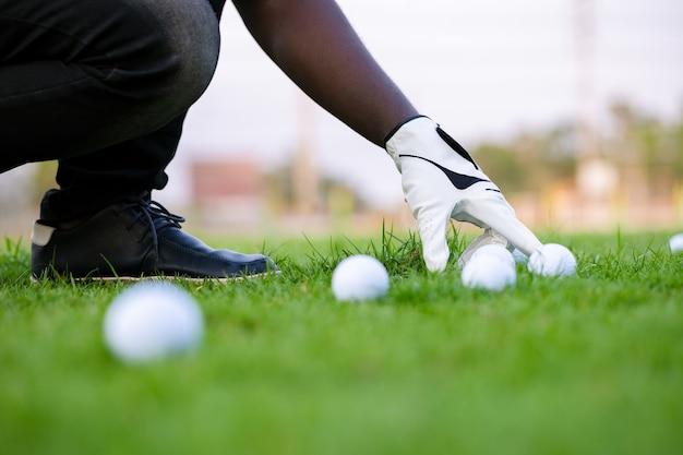 골프 코스에서 클럽과 푸른 잔디에 골프 공을 넣어 손