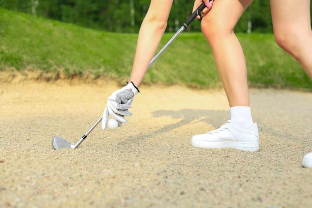 골프 코스에서 티에 골프공을 퍼팅하는 손.