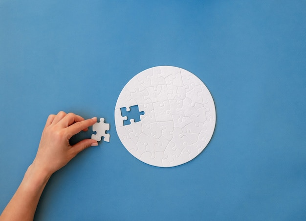Hand putting last piece in white round shaped jigsaw puzzle