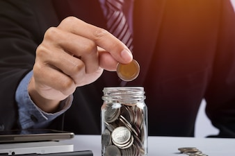 Hand putting mix coins and seed in clear bottle and copyspace, Business investment growth concept.