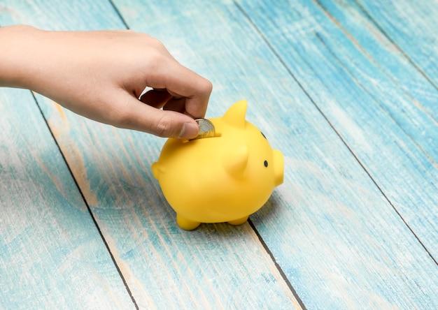 保存と財務の概念のために黄色の貯金箱にお金のコインを置く手