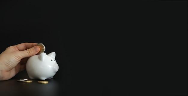 お金を節約するために貯金箱にお金のコインを入れる手。富、予算、投資、財務の概念。テキスト用の空きスペース、コピースペース。貯金箱、黒の背景に貯金箱。