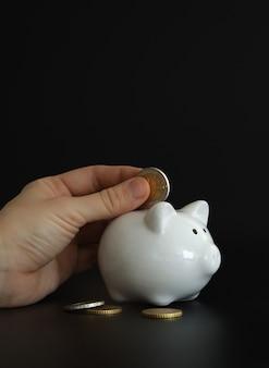 お金を節約するために貯金箱にお金のコインを入れる手。富、予算、投資、財務の概念。貯金箱、黒の背景に貯金箱。