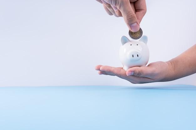 돼지 저금통 절연 회색 배경에 돈 동전을 넣어 손. 부동산 투자 및 주택 모기지 금융 개념.