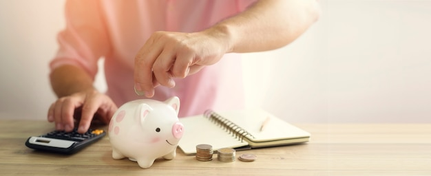 A hand putting money coin into piggy bank. a saving money for future investment concept.
